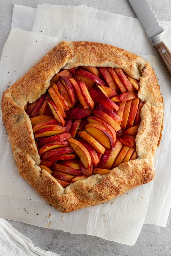 overhead shot of peach galette on parchment paper