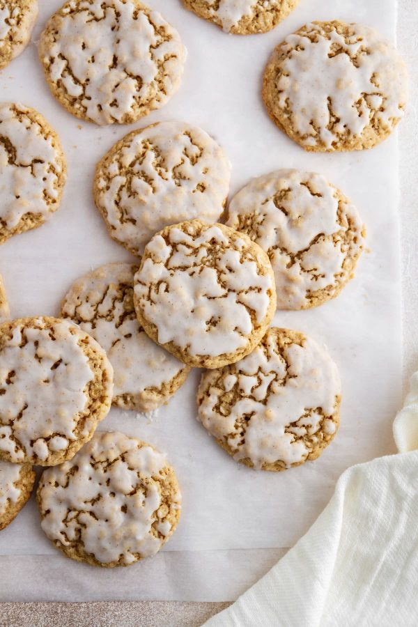 iced pumpkin spice oatmeal cookies on parchment paper