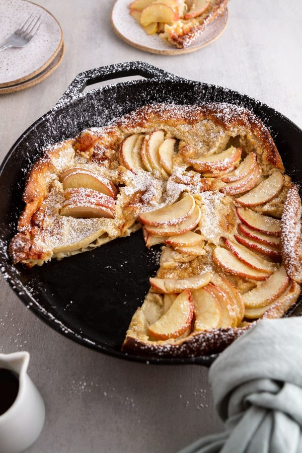 side view of German apple pancake in a cast-iron skillet with a slice taken out